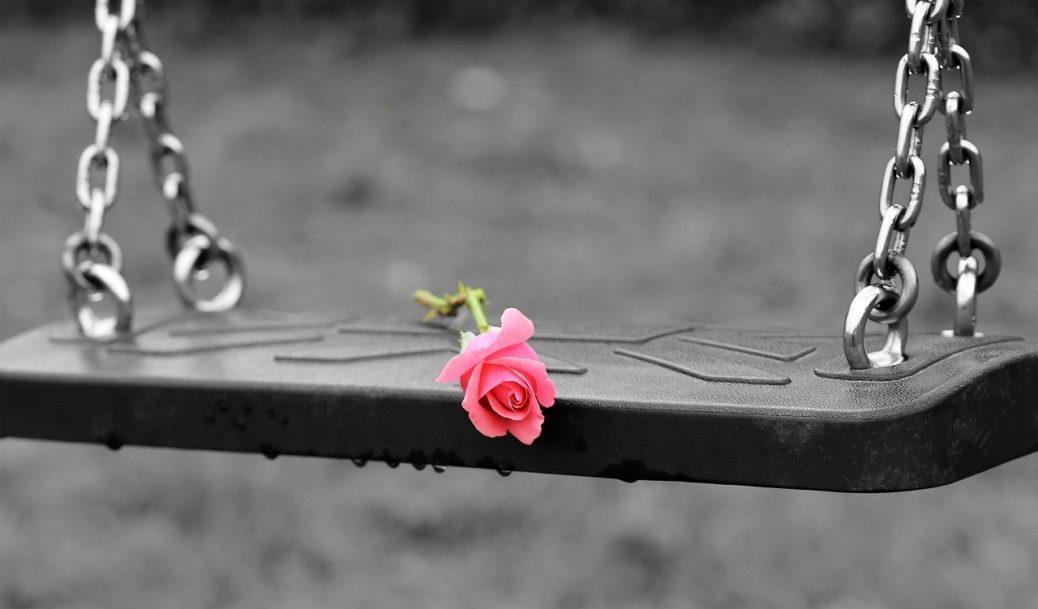 Prázdná houpačka s růží - rány na duši