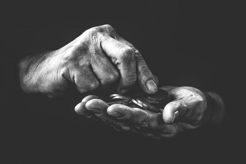 Penzijní reforma - staré ruce počítající mince - peníze - chudoba